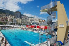 People swim and sunbathe at the open air public swimming pool in Monaco. Royalty Free Stock Photos