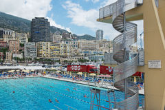 People swim and sunbathe at the open air public swimming pool in Monaco. Royalty Free Stock Photo