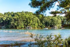 Free People Swimming And Boating In Lake Lanier During Summer Time Along Side Waterfront Properties And Boat Docks Stock Photo - 125484380