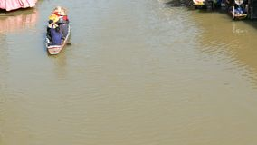 People are swimming in a boat on a brown river to Thailand. A garland of white lamps on a background walking people. Along the shore and riding on a river in a stock footage