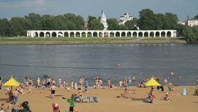 People swimming on the crowded sand beach. Unidentified people swimming in the the Volhov river on the crowded sand beach. Velikiy Novgorod, Russia stock video footage