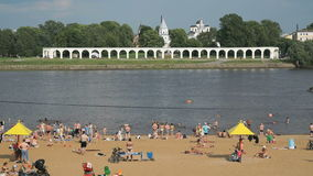 People swimming on the crowded sand beach. Unidentified people swimming in the the Volhov river on the crowded sand beach. Velikiy Novgorod, Russia stock footage
