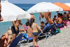 People at the beach summer 2017 greece august. People swimming and having a good time at the beach as temperature rises royalty free stock image