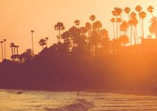Silhouetted People on Beach At Sunset. People swimming at Laguna Beach, California at Sunset Royalty Free Stock Photos