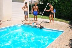 People at swimming pool. Man  throwing  woman to swimming pool Stock Image