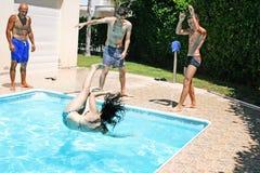 People at swimming pool. Man  throwing  women to swimming pool Royalty Free Stock Photography