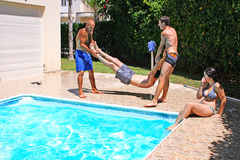 People at swimming pool. Men  throwing  their friend to swimming pool Stock Images