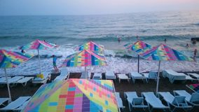 People swimming in the sea in resort city, view of beach with colorful umbrellas. Stock footage stock video