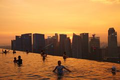 People Swimming in Sky Pool of Marina Bay Sands. Travelers swimming in Sky Park, enjoying the sunset cityscape of Singapore. The Sky Park is on the 57th floor of Stock Images