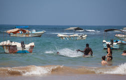 People are swimming and splashing between fishing boats Stock Image