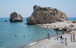 People swimming and walking at  of the Rock of Aphrodite beach, Stock Image