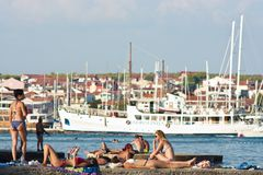 People in swimsuits sunbathing on the pier on the seaside royalty free stock image