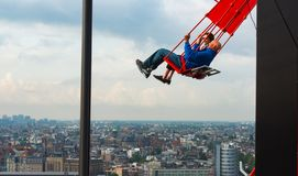 People on the swing on top of A`dam Lookuot, Amsterdam. Panoram of the city in the background Royalty Free Stock Photography