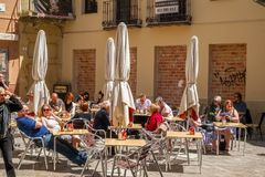 People at tables in the historic center. Malaga, Spain - April 14, 2018. people at tables in the historic center of Malaga city, Spain Stock Image