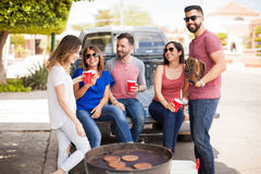 People tailgating at a baseball game. Group of young adults sitting on the back of a pick up truck and talking about a baseball game while drinking and cooking stock photo