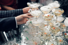 People take the glasses of champagne pyramid. close-up. Pyramid of glasses for champagne at outdoor garden in wedding ceremony stock photo
