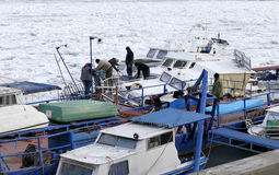 People take out trapped boat from the frozen Danube river Stock Images