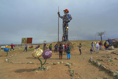 People take pictures near the. Darkhan, Mongolia - MAY, 07 2016: People are photographed near the high sculpture Iron Man, symbol of the city of Darkhan royalty free stock images