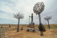 People take pictures near the. Darkhan, Mongolia - MAY, 07 2016: People are photographed near the high sculpture Iron Man, symbol of the city of Darkhan stock photos