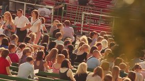 People take  places on tribune at summer event. Stadium. Crowd. Adults, youth. Sunny evening. People sitting and take its places on tribune at summer event stock video footage