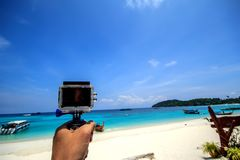 People take seascape with action camera  blue sky background. Royalty Free Stock Photos