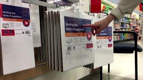 People taking mailing box. Inside Shoppers drug mart store stock video
