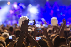 People taking photographs with touch smart phone during a music Stock Photography