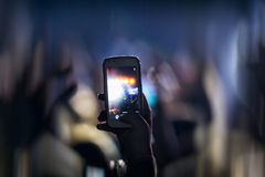 People taking photographs with touch smart phone during a music Royalty Free Stock Photo