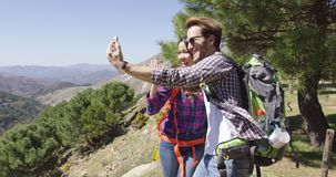 People taking selfie while hiking. Young couple hiking in mountains with backpacks and smiling while taking selfie on background of mountain scape stock footage