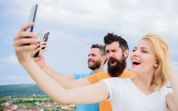 People taking selfie or streaming online video. Mobile internet and social networks. Mobile dependency problem. Girl and. Men with mobile smartphones royalty free stock image