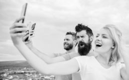 People taking selfie or streaming online video. Mobile internet and social networks. Mobile dependency problem. Girl and. Men with mobile smartphones stock images