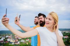 People taking selfie or streaming video. Mobile internet social networks. Mobile dependency problem. Bloggers team. Girl. And men with mobile smartphones stock photography