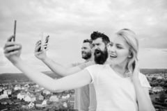 People taking selfie or streaming video. Mobile internet social networks. Mobile dependency problem. Bloggers team. Girl. And men with mobile smartphones royalty free stock photography