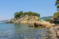 People taking a sunbath and swimming on the coast of the sea stock photos