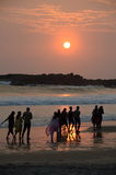 People taking sunset stroll on beach. Some local people taking a stroll on the beach at sunset in Kovalam Beach, Kerala, India Royalty Free Stock Images