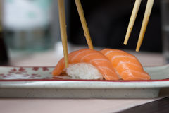 People taking sushi food with chopsticks from a plate. Close-up. View Royalty Free Stock Images