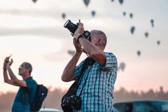 2 people taking with there smartphone and DSLR camera pictures of the climbing hot air balloons while the sky turns red. stock images