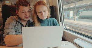 People talk on business using laptop in train. Friends or coworkers in the train. They talking and discussing some question using laptop during their travel stock video footage