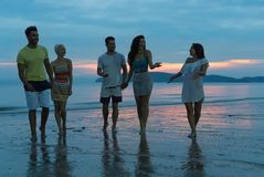 People Talking On Beach At Sunset, Young Tourist Group Walking On Sea In Evening Communication royalty free stock photo