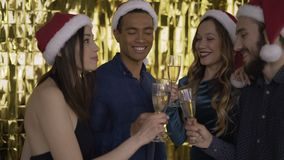 4 people people talking at a christmas party. guys and in red hats Santa Claus. mixed race people. golden background. 4K
