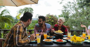 People talking passing food eating on terrace young friends sitting at table outdoors laughing communication stock footage