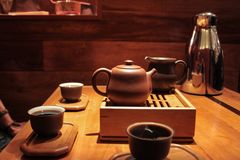 3 people tasting and drinking very dark pu-erh tea into small tasting cups stock image