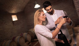 People tasting wine in winery basement Stock Photo