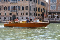 People in taxi boat on canal of Venice, Italy. Venice, Italy - August 13, 2016: People in taxi boat on canal of Venice Royalty Free Stock Photography