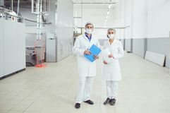 People technologists in masks at food factory. People technologists in masks look into the camera at food factory royalty free stock images