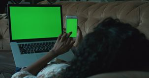 People and technology. Afro-american woman is using the mobile phone with green screen while lying on the sofa with the. Laptop with green screen on her legs stock video