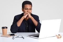 People, technology and career concept. African American man with curly hair, dark skin, keeps hands near mouth, watches stock image