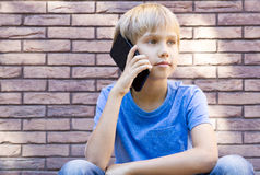 People, technology and communication concept. Child talking on cell phone Royalty Free Stock Images