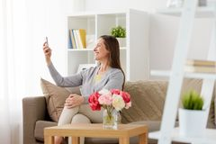 Happy woman taking selfie by smartphone at home Royalty Free Stock Photo