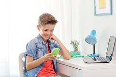 Happy boy with smartphone and laptop at home Stock Photography